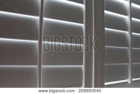Angled Closed White Plantation Shutters And Rod Background