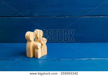 Wooden Figurines Of People In The Shape Of A Family On A Blue Background. The Concept Of Family Valu