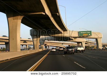 freeways intersect over and under each other with great shadows at the beginning of sunset