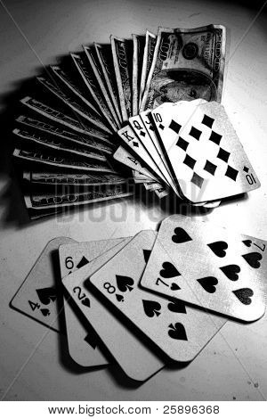 Royal Flush laying on a large pile of cash in $100.00 bills while a loosing hand lays next to it on a white background. 