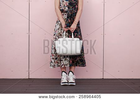 Woman In A Fashionable Dress With A White Stylish Bag Stand Near The Pink Wall. Women's Fashion Snea