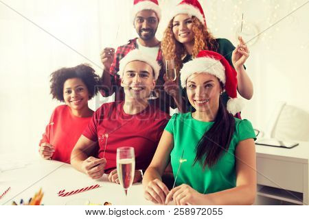 christmas, celebration and holidays concept - happy team in santa hats with sparklers and non-alcoholic sparkling wine at corporate office party