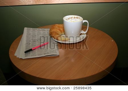 Latte with  croissant   and news paper and whipped cream and chocolate power