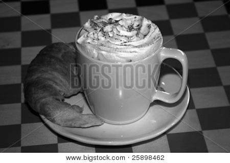 Latte with  croissant  and whipped cream and chocolate power in black and white