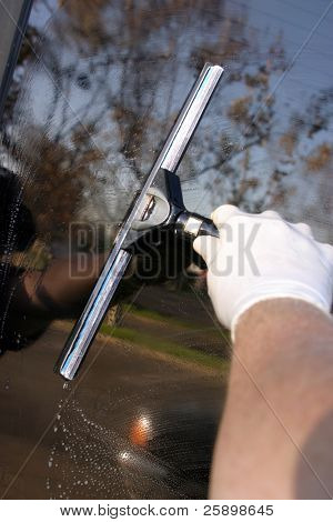 window washer squeegieing off soapy water from a window