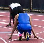 Two male high school sprinters are ready to sprint in lanes three and four during a track and field competition. poster