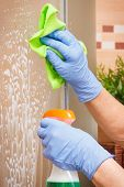 Hand of senior woman in protective gloves cleaning glass shower in bathroom using microfiber cloth and detergent, concept of household duties poster