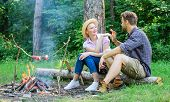 Pleasant smell of roasted food makes picnic atmosphere perfect. Picnic roasting food over fire. Idyllic picnic date. Family enjoy weekend in nature. Couple in love relaxing sit on log having snacks poster