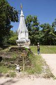 Traveler thai woman travel visit and respect praying Chedi or stupa Phra That Kong Khao Noi at Wat Phra That Kong Khao Noi in Yasothon, Thailand poster