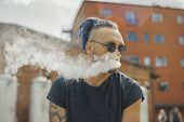 Portrait of young vaping man with dreadlocks. Vapor concept. Vaping e-Cigarette poster