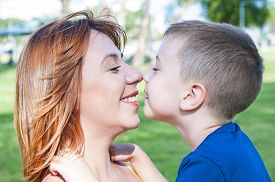 Young And Beautiful Caucasian Woman And Her Son Touching Each Other Nose To Nose, Face To Face Close