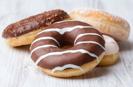 Heap Of Various Doughnuts On White Wooden Background