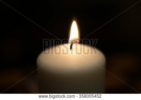 Mourning candle of sadness and longing. Festive fire macro background.