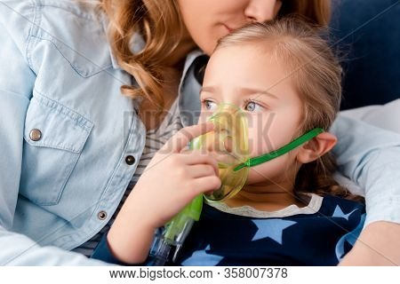 Mother Kissing Asthmatic Daughter In Respiratory Mask