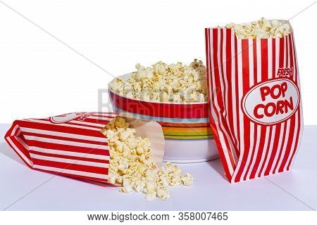 Horizontal Shot Of A Bowl Of Popcorn With One Bag Of Popcorn Leaning Against It And A Second Bag Of