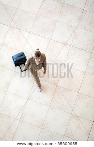 overhead view of young woman walking at airport