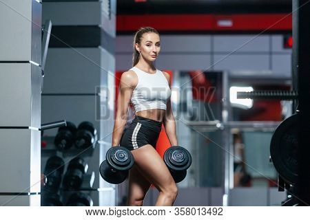 Photo Of A Sexy Muscular Girl Posing Holding Two Heavy Dumbbells In The Gym