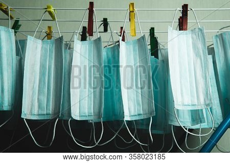 Lots Of Medical Masks That Are Dried On The Dryer On The Clothespins. Concept Of The Problem Of The
