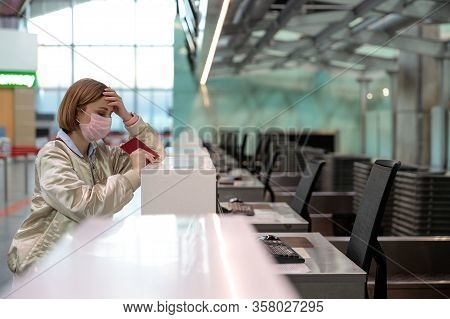 Woman With Luggage Over Flight Cancellation, Stands At Empty Check-in Counters At Airport Terminal D