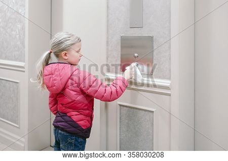 Caucasian Girl Pushing Elevator Button With Disinfecting Wet Wipe. Precaution Against Virus Spread.