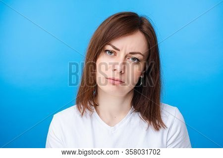 Pretty Caucasian Woman Showing Discontent. Light Blue Background