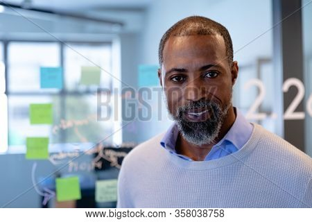 Portrait of a mixed race man wearing smart clothes, working in a modern office, smiling and looking straight into a camera. Social distancing and self isolation in quarantine lockdown