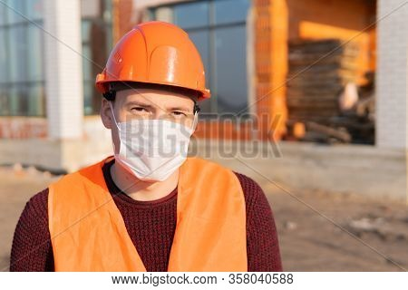 Portrait Of Male Construction Worker In Medical Mask And Overalls On Background Of House Under Const