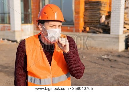 Male Construction Worker In Overalls And Medical Mask Coughing On Background Of House Under Construc