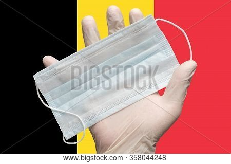 Doctor Holds Medical Face Mask In Hand In White Gloves On Background Colors Flag Of Belgium. Concept
