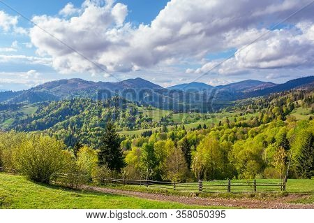 Beautiful Rural Landscape In Mountains. Fence Along The Path Through Fields And Meadows On Hills Rol