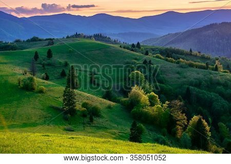 Mountainous Countryside In Springtime At Dusk. Trees On The Rolling Hills. Ridge In The Distance. Cl