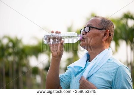 A Happy Old Asian Man Is Drinking Water At Park With Sunlight. Healthcare And Senior Sports Concept.