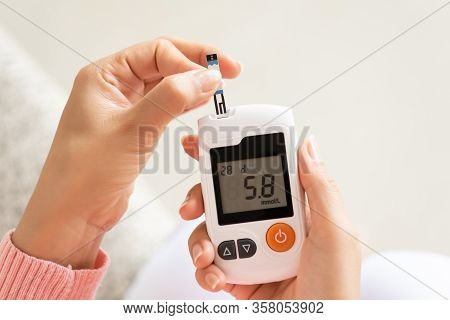 Close Up Of Woman Hands Checking Blood Sugar Level By Glucose Meter For Diabetes Tester Using As Med