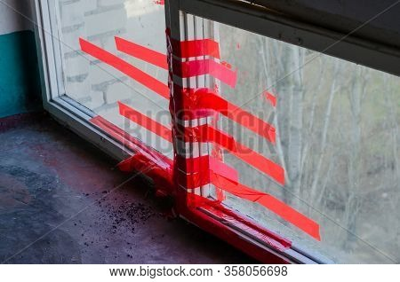 Two Windows Are Fastened With Red Duct Tape. A Pile Of Cigarette Ash On The Floor By The Window. Dir