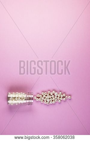 A Small Glass Jar Filled With Pearl Beads, Close-up. Pearls Scattered On A Pink Background