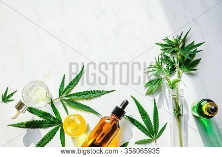 Various Glass Bottles With Cbd Oil, Thc Tincture And Hemp Leaves On A Marble Background. Flat Lay, M