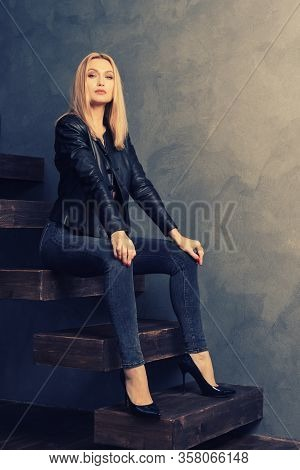 Beautiful Woman In A Black Leather Jacket And Jeans Posing Sitting On A Wooden Cantilever Ladder. Pe