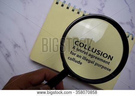 Collusion Meaning Concept Write On A Book Isolated On Office Desk.