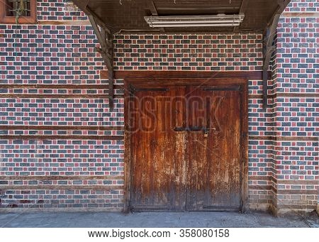 Grunge Wooden Decorated Arched Entrance Gate With Wooden Canopy Above On Wall With Black And Red Bri
