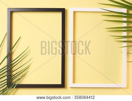 Summer Concept - Two Photo Frame And Palm Leaves On Pastel Yellow Background