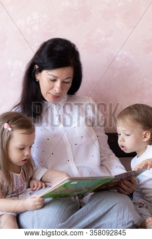 Young Grandmother Reads A Book To Her Little Grandchildren. Young Beautiful Grandmother Spends Time