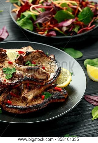 Homemade Grilled Pork Loin Chops In Lemon Sauce With Herbs On Rustic Wooden Table