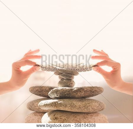 Womans Hands Put A Feather On A Pyramid Of Stones. Equilibrium, Balance Concept. Zen Stones On White