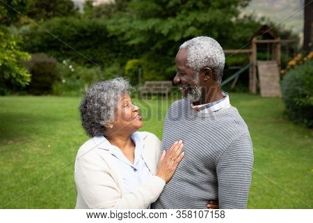 Side view of senior African American couple in the garden, embracing and looking at each other. Family enjoying time at home, lifestyle concept