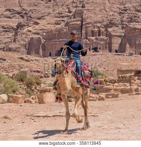 Young Man, Jordanian Riding A Camel. Travel Genre Photography In Petra, Jordan