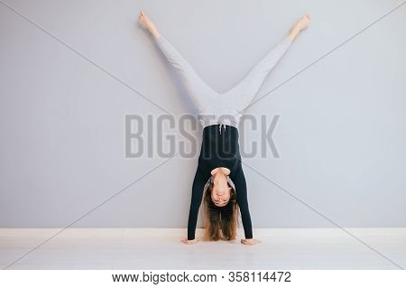 Fit Woman Doing Handstand Near Wall. Athlete Standing On Hands Concept Balance Sport Fitness