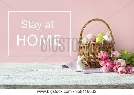 Wicker Basket With Easter Eggs And Pink Tulips. Spring Easter Pink Background. Slogan - Stay At Home