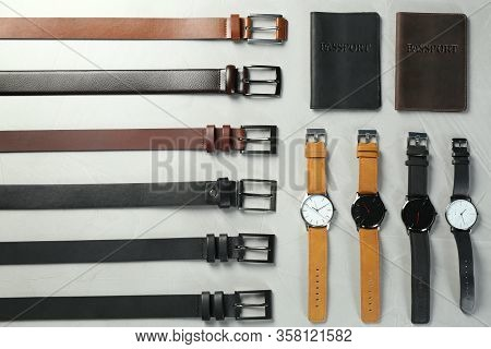 Leather Belts, Passports Cases And Wristwatches On Grey Stone Table, Flat Lay