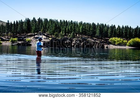 A Fisherman Inside A Lake Surrounded By Pine Trees And Mountains In The Province Of Neuquén, Argenti