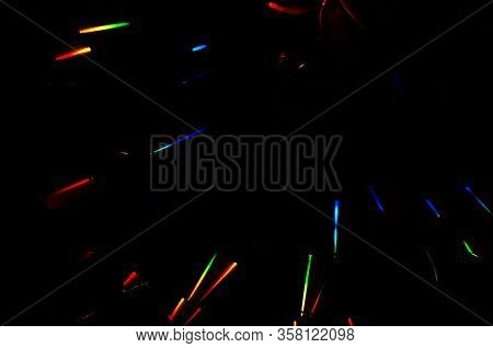 Abstract Dark Background Of Rainbow Iridescent Light Streaks. Prismatic Color Light Streaks